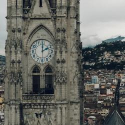 Two towers flanking a church both with clocks showing different times