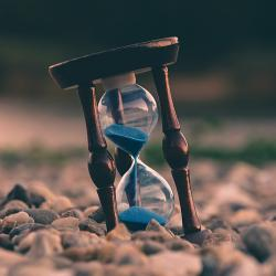 An hourglass resting on pebbles running out of sand