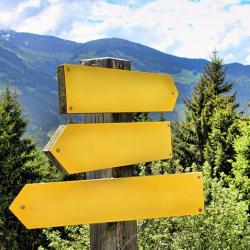 Yellow signpost in the mountains pointing in different directions