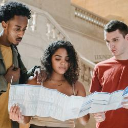 Three students poring over a timetable or map