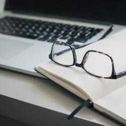 Pair of glasses and a pen lying on a notebook next to a laptop