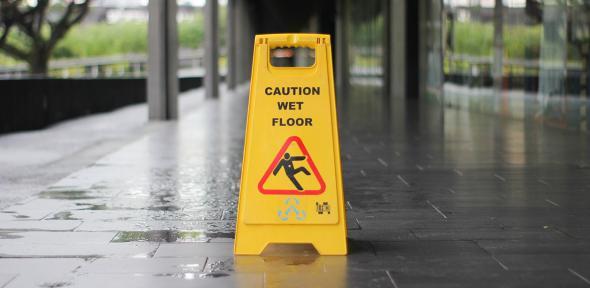 A wet floor caution cone on a train platform