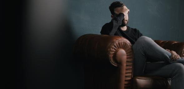 Man on sofa looking distressed with head in hand
