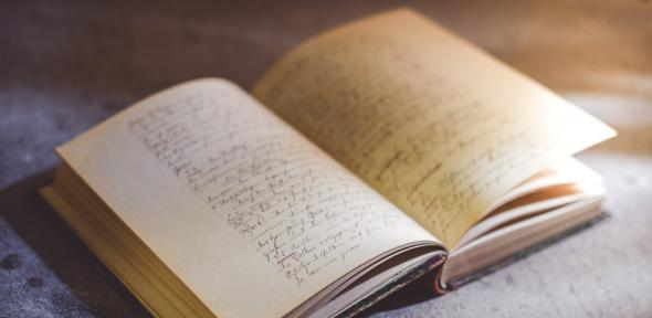 An ancient book open to a page covered in handwriting